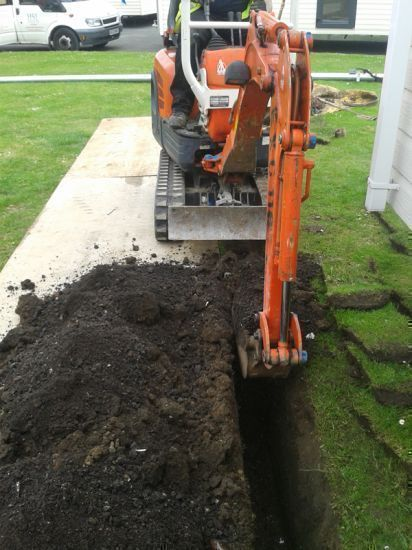 Digger excavating trench work: Swipe To View More Images
